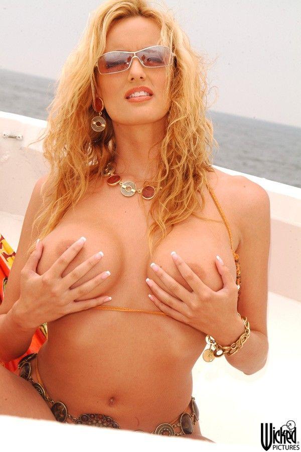 Мамочка-блондинка Stormy Daniels показывает крупную голенькую грудь на яхте