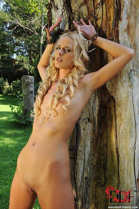 Кудрявая светловолосая девушка прикована к дереву